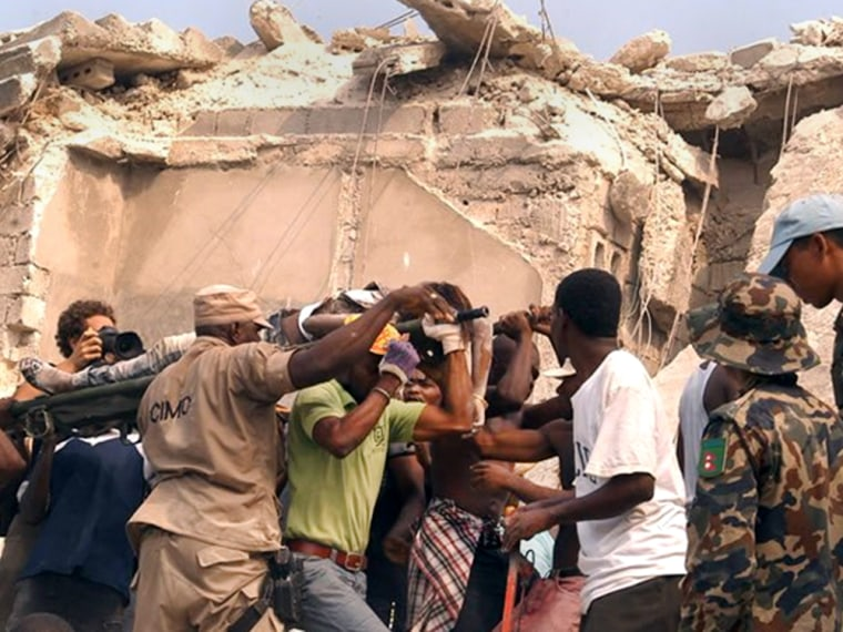 Image: People carry an injured person after an earthquake in Port-au-Princ