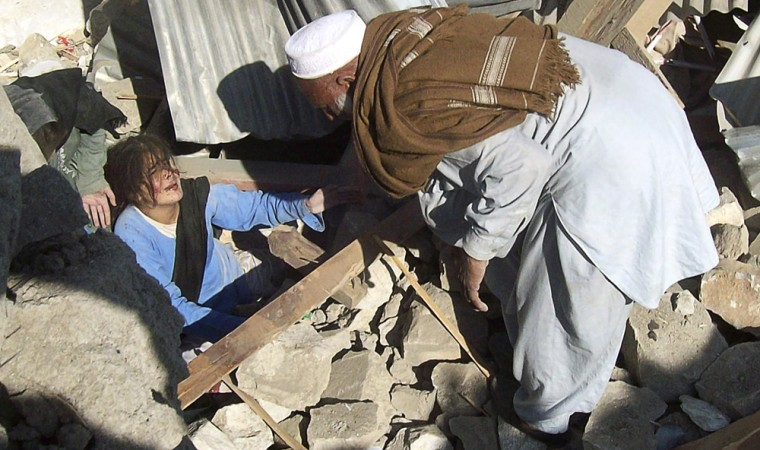 Image: A resident attempts to rescue female students from the rubble of a bombed school