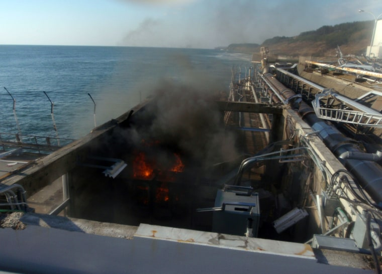Image: Fire and smoke are seen at a building for sampling from seawater near No.4 reactor of the Tokyo Electric Power Co.'s Fukushima Daiichi Nuclear Power Plant in Fukushima Prefecture in this handout photo