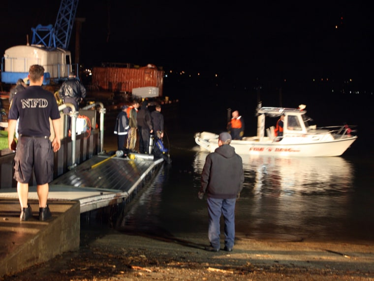 Image: Rescue workers search the scene where a woman drove her minivan into the Hudson River