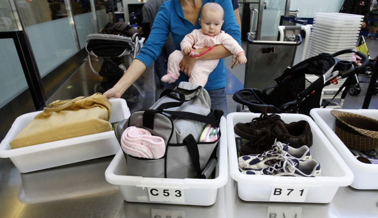 Image: A passenger holding her baby prepares to go through a security checkpoint at Los Angeles International Airport (©MArio Anzuoni / Reuters file)