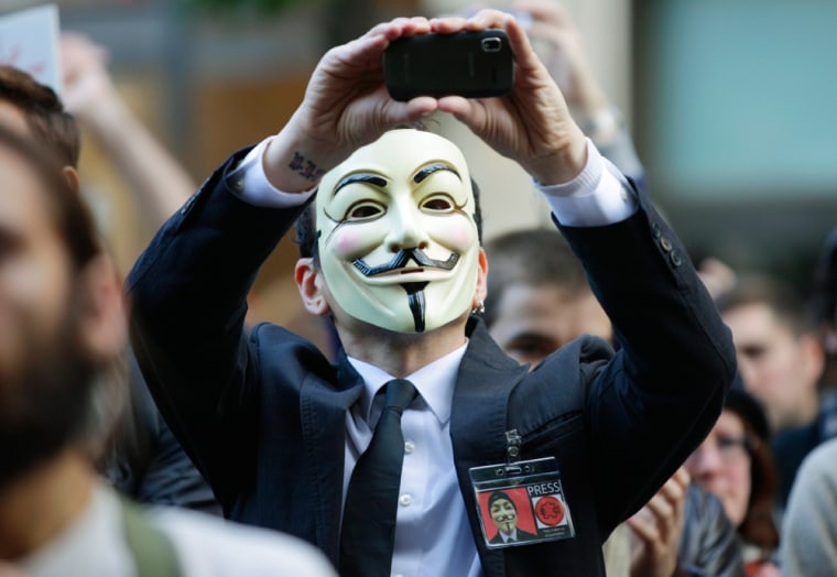 """Image:A protester with the \""""Occupy Seattle\"""" movement wears a mask and takes a photo with a mobile phone."""