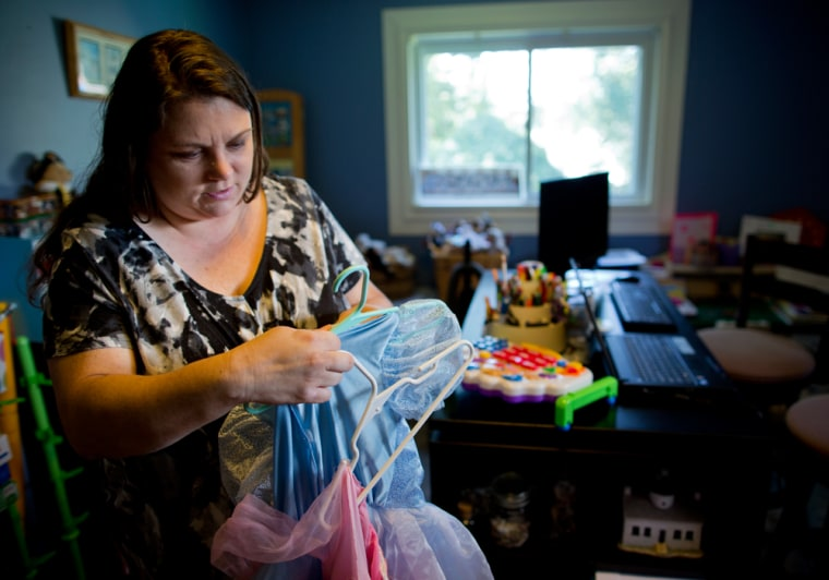 Image:  Mary Conti of Pittsburgh, PA., sorts through her daughters' princess dresses before listing them for sale on a consignment web site.