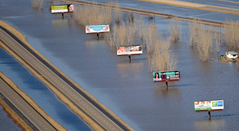 Image: Red River flood waters overtake Highway 29 and it's billboards