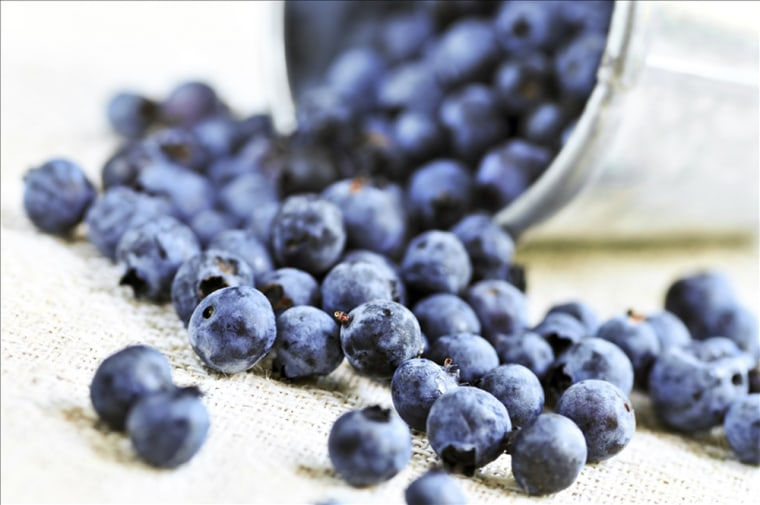 Fresh blueberries spilling out of a pail close up