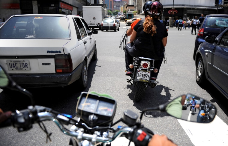 """Image: Drivers of \""""mototaxis\"""" (motorcycle taxis) transport clients"""