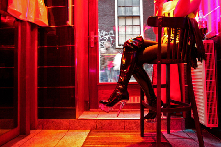 Image: A prostitute waits for clients behind her window in the red light district of Amsterdam
