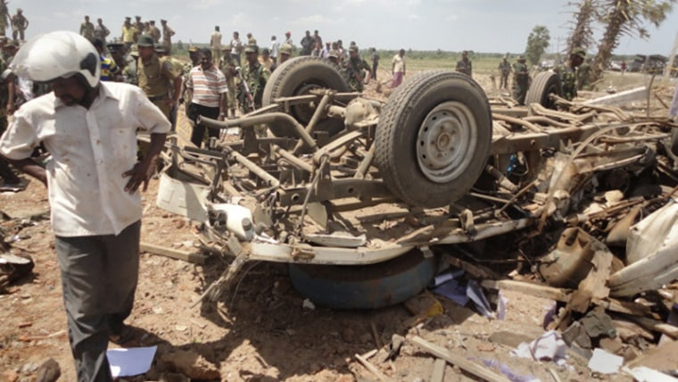 Image: A man stands next to a truck destroyed in an explosion in Batticaloa