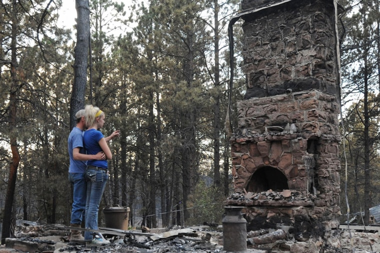 Image: Jaycie Francis, right, looks at the spot where she used to sit at her aunt's house and watch television as she is comforted by her boyfriend, James Folk, in Black Forest, Colo., on June 13.