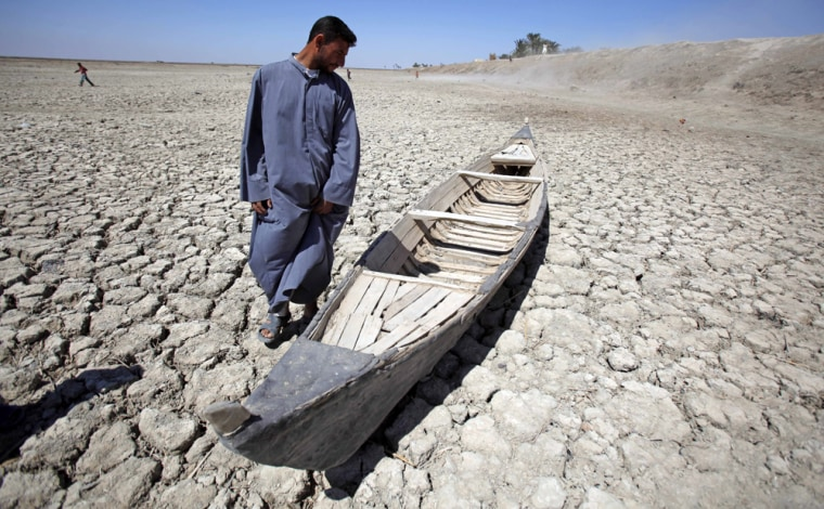 Image: Akeed Abdullah stands next to his boat in a dried marsh in Hor al-Hammar in southern Iraq