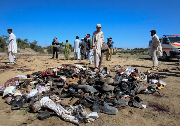 Image: A man stands next to sandals at the site of a suicide bomb attack on the outskirts of Peshawar