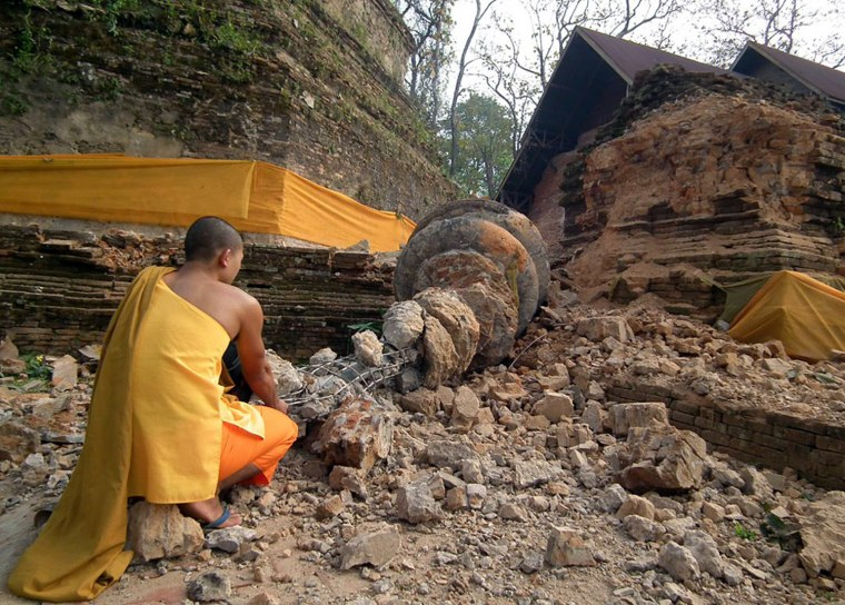 Image: A Thai Buddhist monk looks on a collapsed 800-year-old pagoda damage caused by the Myanmar 6.8-magnitude earthquake at Wat Chedi Luang temple, Chiang Rai province near the Thai-Myanmar border in northern Thailand