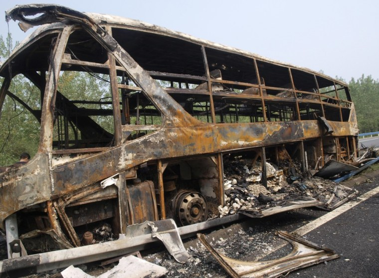 Image: The wreckage of a bus which caught fire is seen on the Beijing-Zhuhai Highway in Xinyang