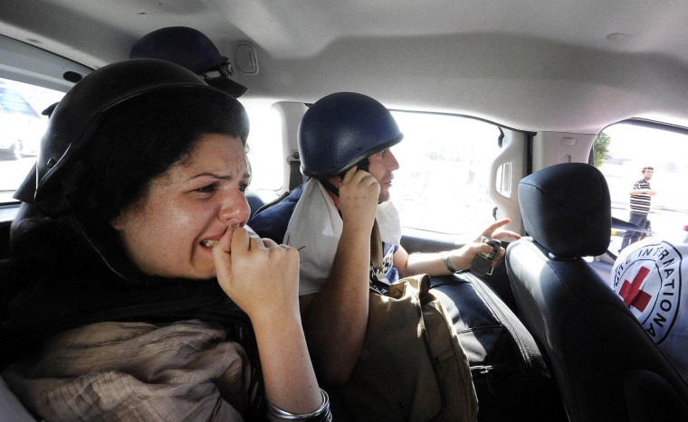 Image: Jomana Karadsheh and Matthew Chance from CNN are evacuated by the International Red Cross from the Rixos hotel in Tripoli