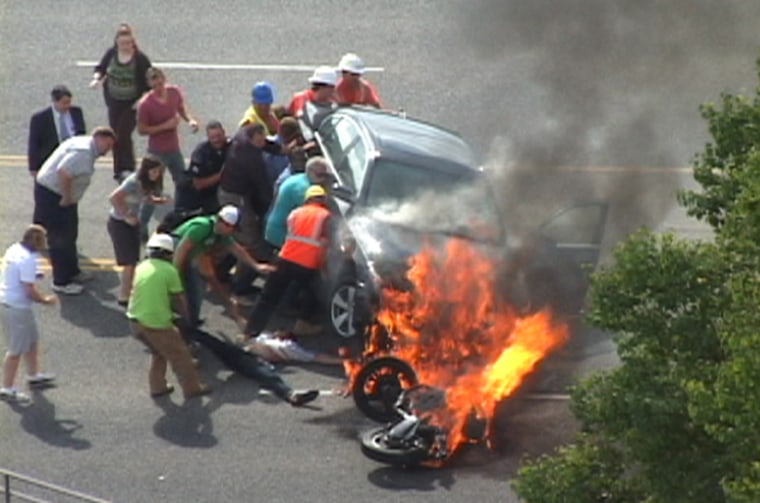 A group of people tilt a burning BMW up to free Brandon Wright, on his back on the ground, who was pinned underneath Monday after he collided witha car while riding his motorcycle on U.S. 89 in Logan, Utah.