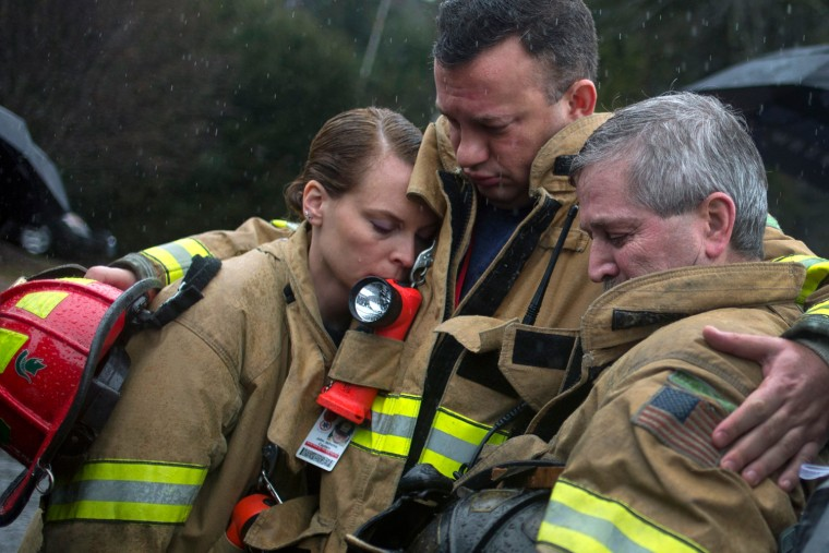 Sandy Hook Village firefighters observe a moment of silence near Sandy Hook Elementary in Newtown, Conn., on Dec. 21. Many Americans remembered the victims of the Newtown, Connecticut, school massacre with a moment of silence on Friday, as a powerful U.S. gun rights lobbying group prepared to plunge into the national debate over gun control.