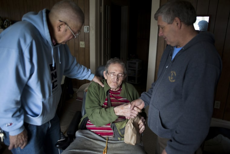 """Edward McClatchen, left, and Mike Turner, right, pray with Frank Hill, center. Frank lives alone, but looks forward to seeing Turner every week. """"No matter when I see him, no matter what is happening to him, he is always smiling,"""" said Turner."""