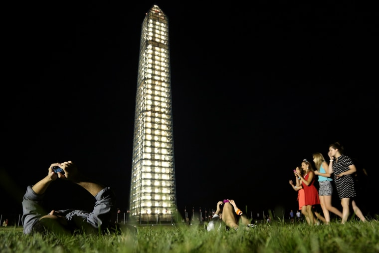 Image: Visitors lie on grass beneath the newly-lit Washington Monument in Washington