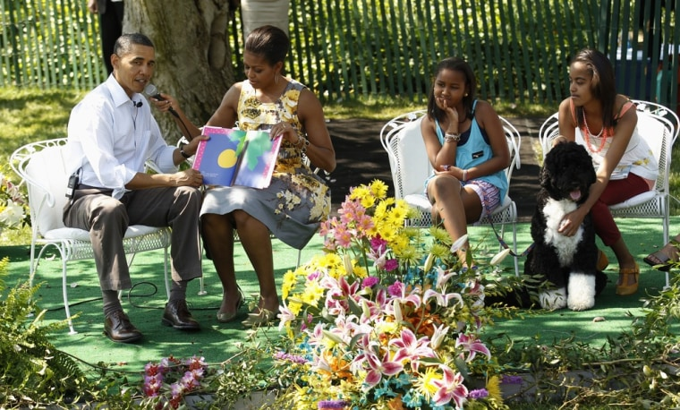 Image: U.S. President Barack Obama and First Lady Michelle Obama read a book as daughters Sasha and Malia listen on with Bo during the Easter Egg Roll at the White House