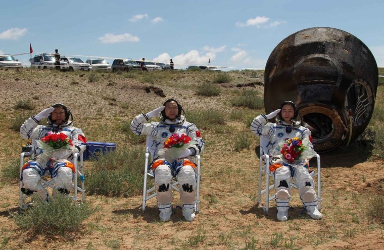 Image: Chinese astronauts Jing Haipeng, Liu Wang and Liu Yang, China's first female astronaut, salute in front of the re-entry capsule of China's Shenzhou 9 spacecraft in Siziwang Banner, Inner Mongolia Autonomous Region