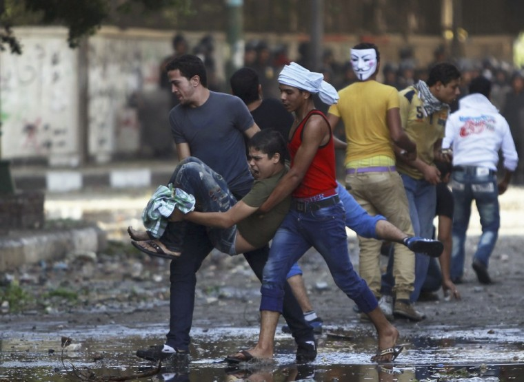 Image: Protesters carry an injured man who was hurt during clashes along a road leading to the U.S. embassy, near Tahrir Square in Cairo