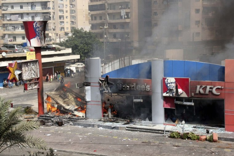 Image: Hardee's and a Kentucky Fried Chicken fast food outlet burns after protesters set the building on fire in Tripoli, northern Lebanon