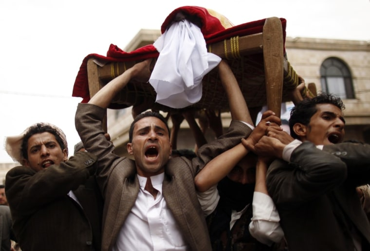 Image: Mourners shout slogans as they carry the coffin of Mohammed al-Tuwaiti in Sanaa