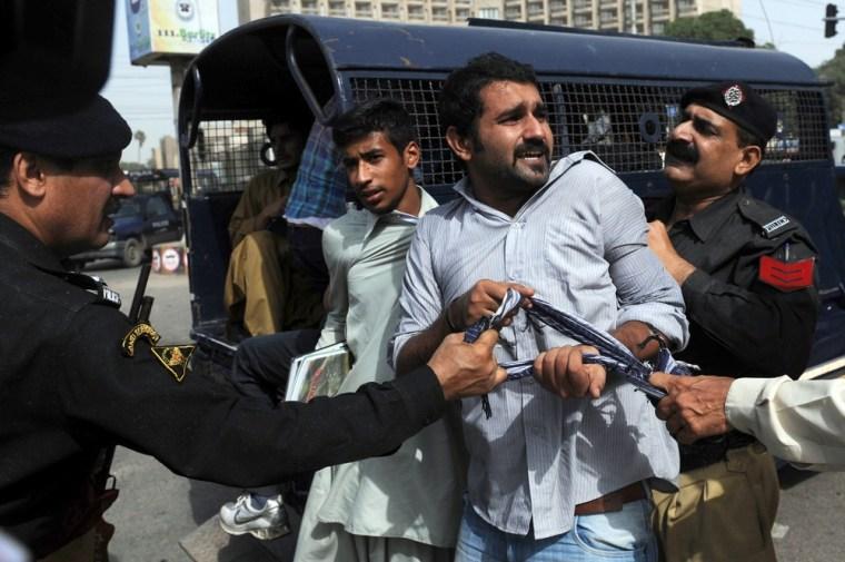 Image: Pakistani policemen arrest activists.