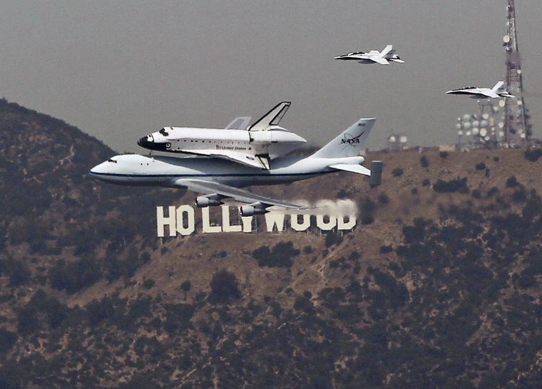 Image: The Space Shuttle Endeavour is escorted by two F18 jets as it passes the Hollywood sign on the back of a 747 on its arrival in Los Angeles