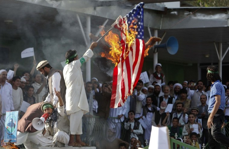Image: Afghan protesters set fire to a U.S. flag as they shout slogans during a demonstration in Kabul