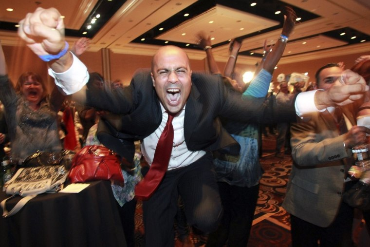 Image: Ajay Narayan cheers as the race is called for U.S. President Barack Obama by a television network during the Nevada State Democrats' election night party at the Mandalay Bay Resort in Las Vegas