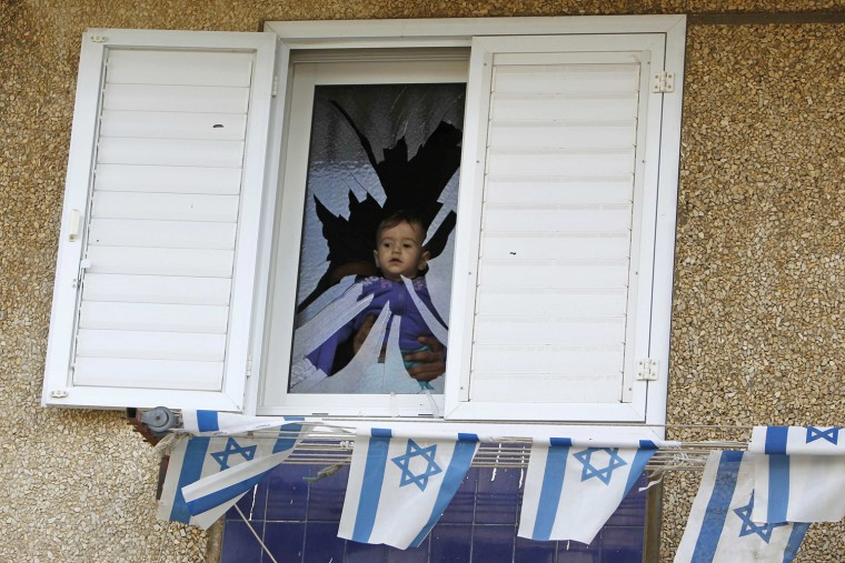 Image: A baby is seen at a broken window after a rocket fired by Palestinian militants in Gaza hit a house in the southern town of Netivot