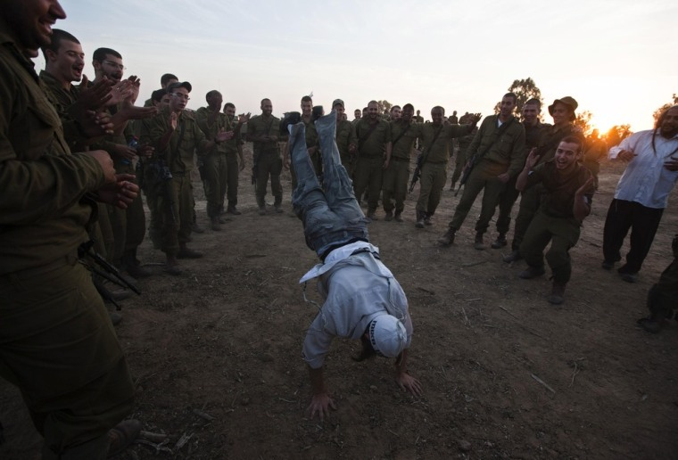 Image: Israeli troops cheer as a Hasidic Jewish man dances during a visit to support the soldiers near the border with Gaza
