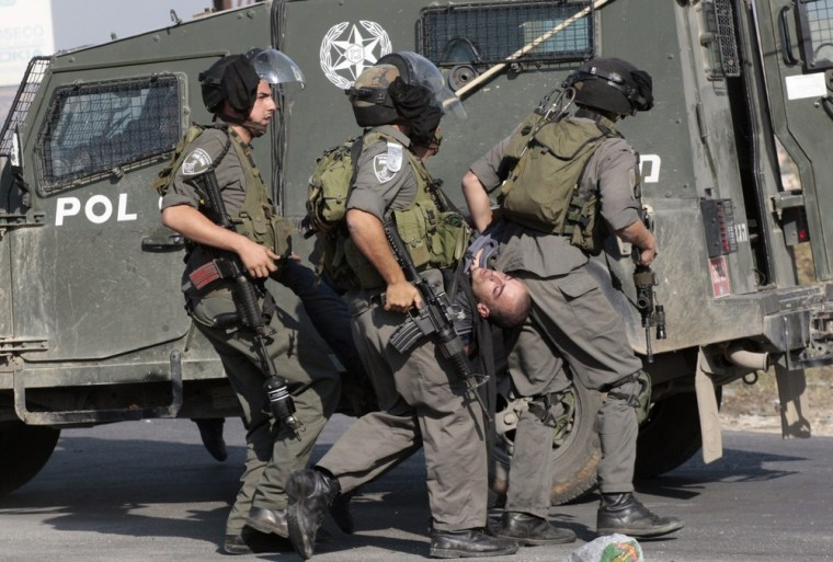 Image: Israeli border policemen carry a stone-throwing Palestinian protester as they detain him during clashes against Israel's military operation in the Gaza Strip, at a checkpoint near Nablus