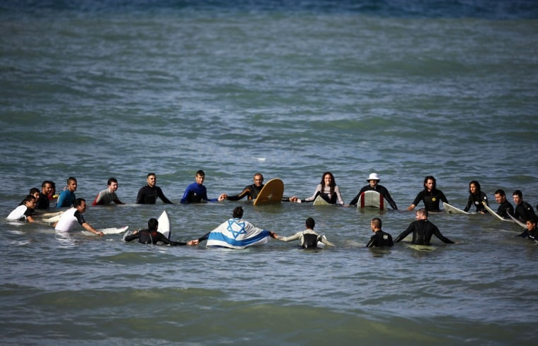 Image: Israeli surfers gather in a circle off shore in the Mediterranean near the city of Ashkelon