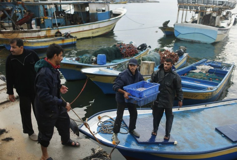 Image: A Palestinian fisherman carries a box containing fish at Gaza Seaport in Gaza City