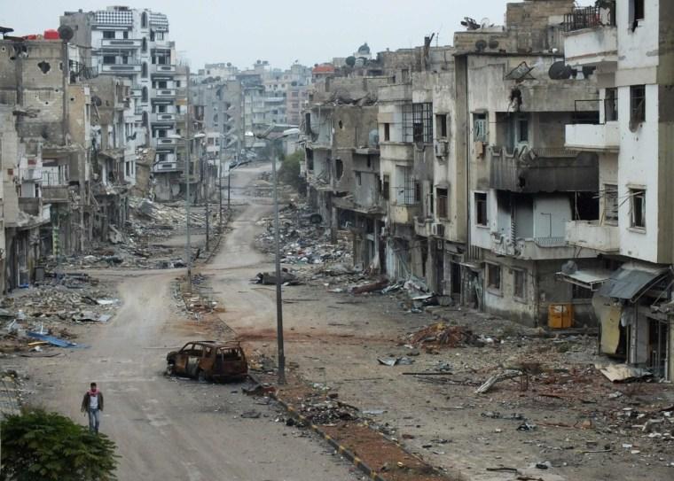 Image: A man walks past a burnt car and damaged buildings along a street at the al-khalidiya neighbourhood of Homs