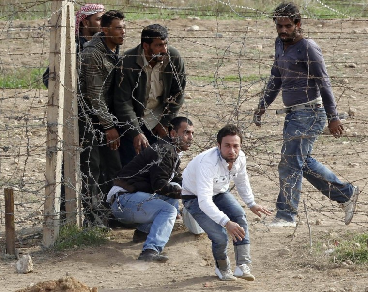 Image: Syrian refugees try to cross the border fence from the northern Syrian town of Ras al-Ain into Turkey during an air strike on Ras al-Ain, in the Turkish border town of Ceylanpinar