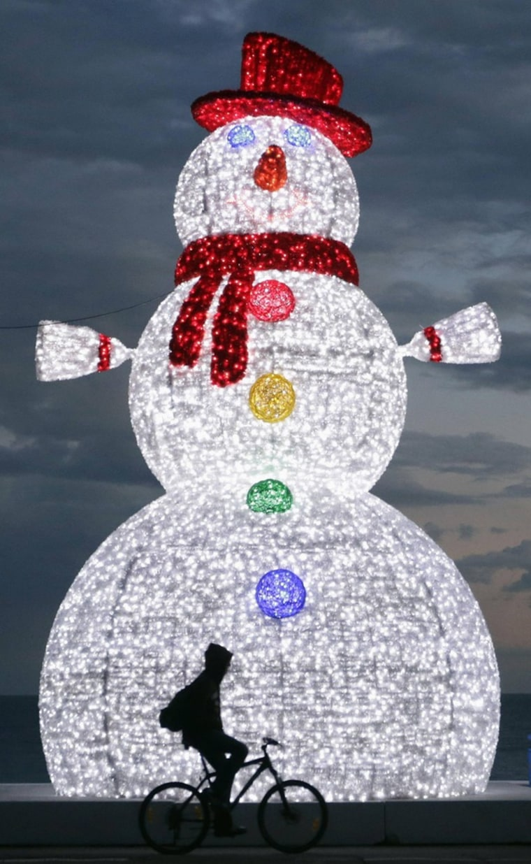 Image: A cyclist rides past a giant illuminated snowman displayed as part of holdiday season decorations on the Promenade des Anglais in Nice