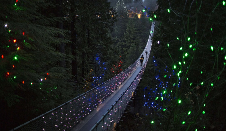Image: Visitors walk across the Capilano Suspension Bridge decorated in Christmas lights in North Vancouver