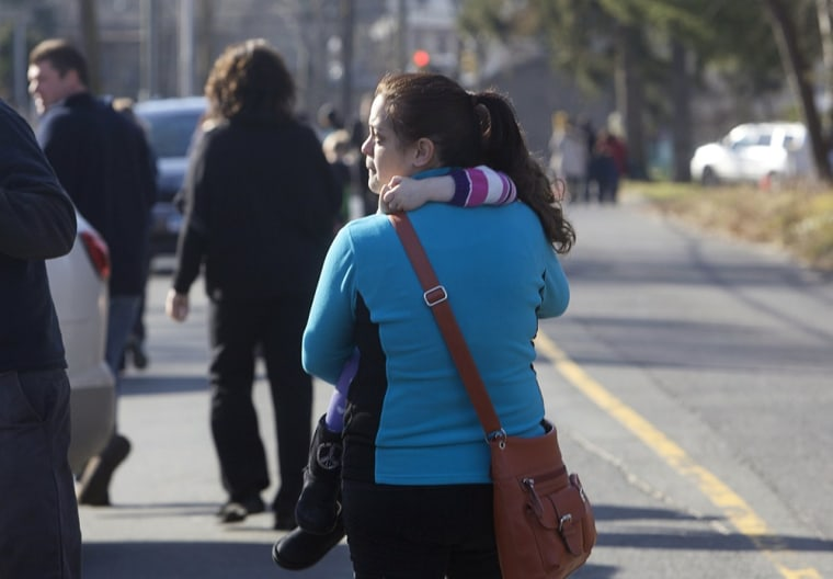 Image: A woman carries her daughter following a shooting at Sandy Hook Elementary School in Newtown