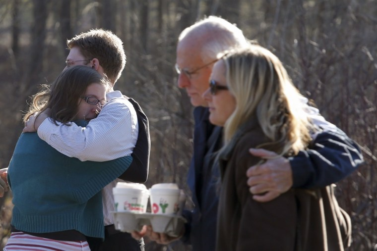 Image: Family members hug outside Sandy Hook Elementary School after a shooting in Newtown, Connecticut