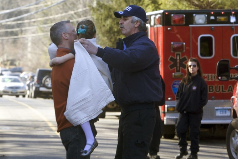 Image: A young girl is given a blanket after being evacuated from Sandy Hook Elementary School following a shooting in Newtown