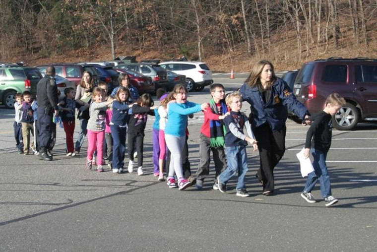 Image: Handout photo of state police personnel leading children from the Sandy Hook elementary school in Newtown