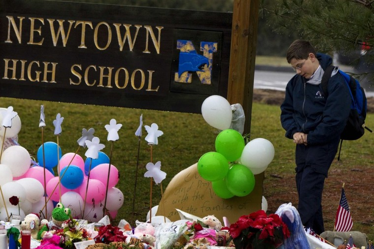 Image: Student pauses after placing flowers at a memorial at the entrance to Newtown High School in Newtown, Connecticut