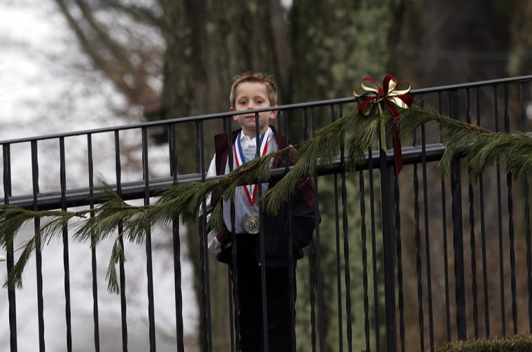 Image: Boy waits to enter Honan Funeral Home, where the family of six-year-old Jack Pinto was holding his funeral service, in Newtown, Connecticut