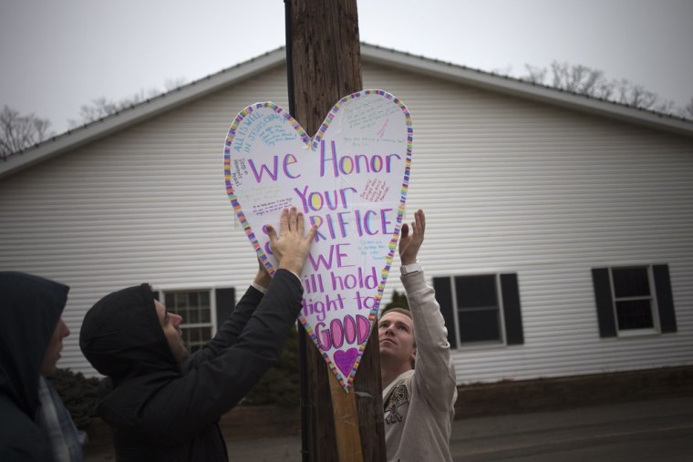 Image: Visitors hang a sign on a light pole along a road leading to Sandy Hook Elementary School in Newtown, Connecticut