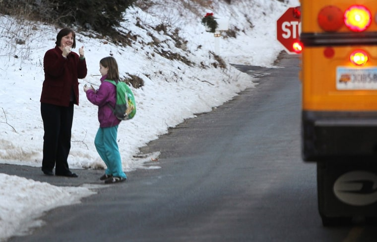Image: A parent greets her child as she got off a school bus returning from the new Sandy Hook School in Sandy Hook