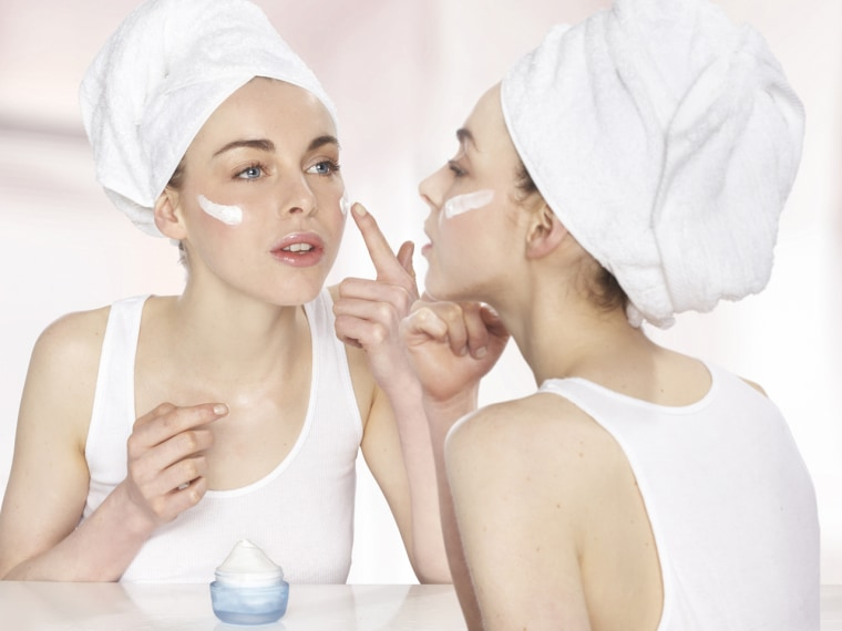 Lady applying lotion while looking at the mirror