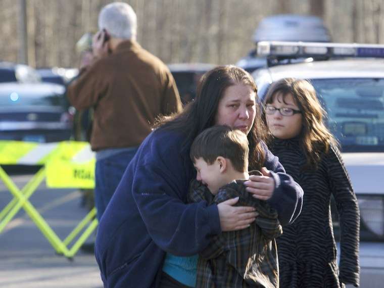 Image: A young boy is comforted outside Sandy Hook Elementary School after a shooting in Newtown